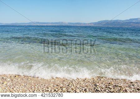 Beautiful Pebbles Beach With Waves And Blue Sky In Brac Croatia