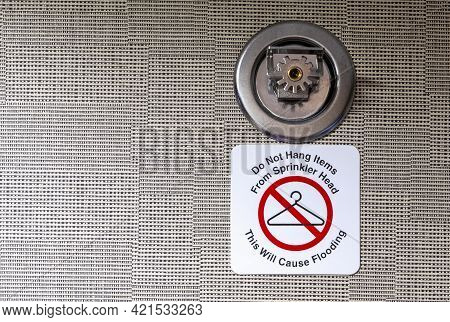 Do Not Hang Items On Sprinkler Head, This Will Cause Flooding Sign Attached To A Wall Mount Metal Fi