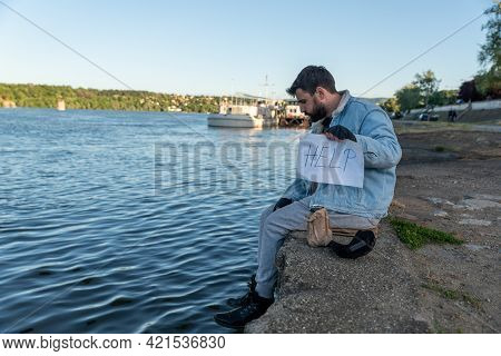 Young Depressed Sick Alcoholic Homeless Man Sitting In The Dockyard Drinking Alcohol Drink And Holdi