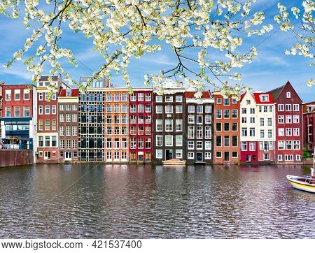 Traditional Amsterdam Architecture On Damrak Canal In Spring, Netherlands