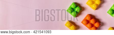 Multicolored Plastic Kids Constructor On Blue Background. Colored Childrens Bricks For Construction.