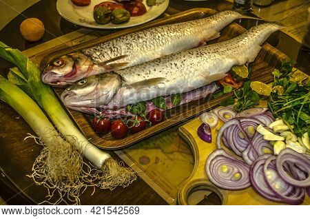 Two Peeled Pollock Fish, Stuffed With Herbs,lemon Wedges With Spices On A Tray Next To Leeks,tomatoe