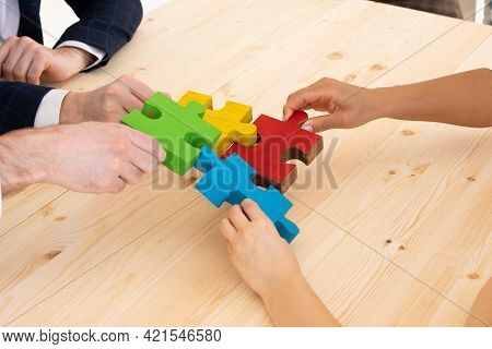 Multi-ethnic Group Of People Assembling Jigsaw Puzzle Together, Hands Joining Pieces At Desk, Succes