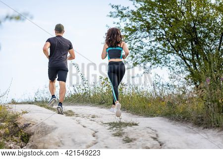 Back View Of Couple Or Friends Running Outdoors