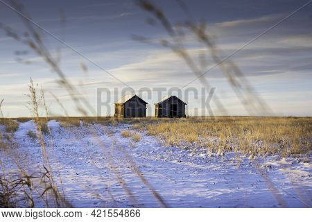 Two Vintage Grain Sheds On A Harvested Field During The Spring At Sunrise In Rocky View County Alber