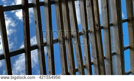 A Wooden Pergola Roof At A Park With Bright Blue Skies And White  Clouds.