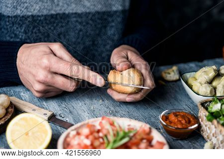 a young caucasian man cuts a bread bun to prepare a sandwich or some vegan appetizers, sitting at a gray wooden table, next to a bowl with a tomato salad and other vegan ingredients