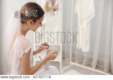 Young Bride Writing On Her Shoe Indoors, Space For Text. Wedding Superstition