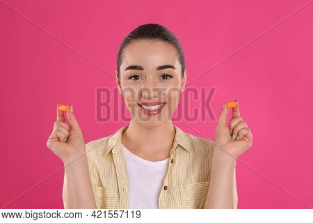 Young Woman With Foam Ear Plugs On Pink Background