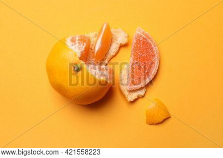 Fresh Tangerine With One Jelly Candy As Its Segment On Orange Background, Flat Lay. April Fools' Day