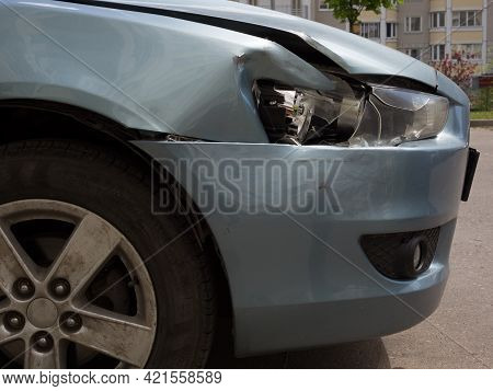 Damaged Sedan Body. Wing And Bumper With Dents And A Broken Right Headlight Of A Car.
