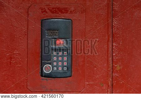 An Intercom On Old Painted Red Steel Surface With A Keypad, Digital Display And Rfid Sensor For Call