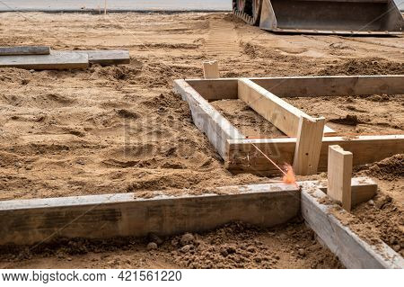 A Wooden Form For Cement Placement In The Brown Dirt At A Construction Job Site. Two By Four Boards,