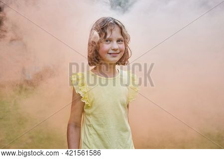 A Blonde Girl With A Short Haircut Stands In A Orange Smoke, Looks At The Camera