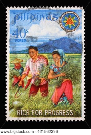 ZAGREB, CROATIA - SEPTEMBER 18, 2014: Stamp issued in the Philippines shows President and Mrs. Marcos harvesting miracle rice, Series: Rice for Progress, circa 1969