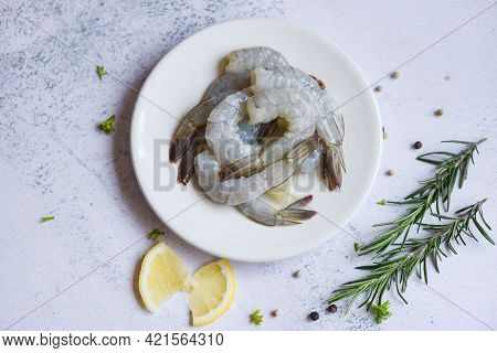Shrimp Peeled On White Plate Ready For Cooking With Herbs And Spices Lemon, Fresh Shrimps Or Prawns