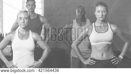 Composition of men and women exercising in fitness class in black and white. sport, fitness and active lifestyle concept digitally generated image.