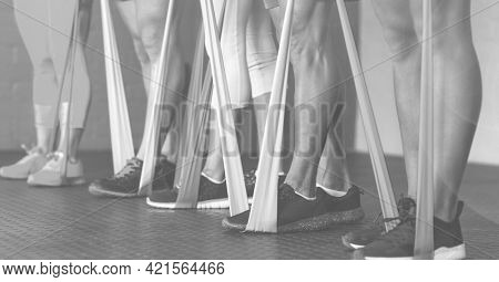 Composition of low section of women exercising with rubber bands in fitness class in black and white. sport, fitness and active lifestyle concept digitally generated image.