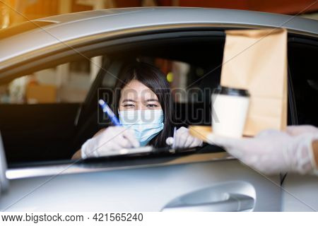 Woman Sign For Delivery Food In Car,safety Food During Coronavirus Pandemic Situation,drive Thru Ser