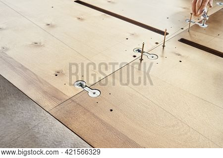 Skilled Craftsman Assembles Large Wooden Dining Table Turning Worktop Connector With Wrench Outdoors