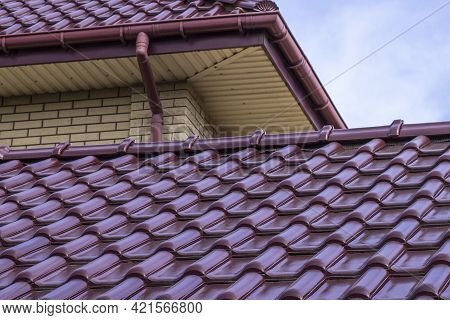 Roof Structure Covered With Red Metal Tiles On A Bright Sunny Day. Modern Housing Construction. Type