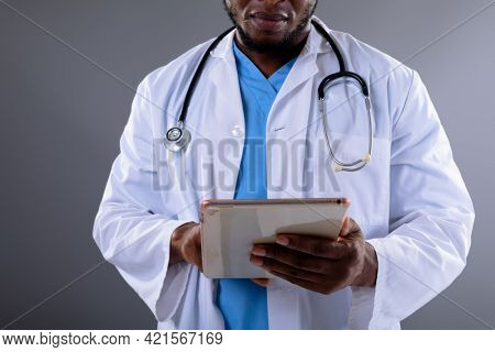 Mid section of african american male doctor using digital tablet against grey background. healthcare and medical professionalism concept