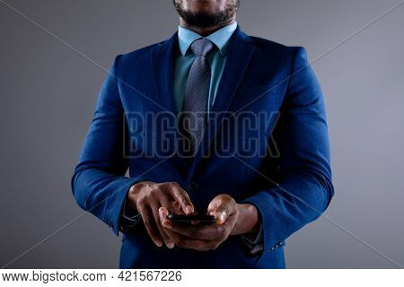 Mid section of african american businessman using smartphone against grey background. business, professionalism and technology concept