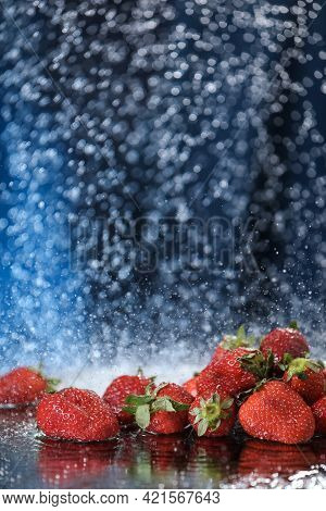 Strawberries Closeup Under The Water Drops In A Dark Blue Background. Healthy Lifestyle. Multivitami