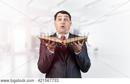 Surprised Businessman Holding Open Book And Looking At Camera. Startled Adult Man In Business Suit A
