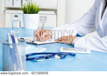 Doctor Filling Patient History List At Clipboard. Physician In Medical Uniform Working At Desk In Of
