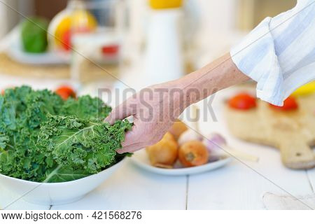 Cropped Close Up Shot Of Retired Woman In Apron Preparing Fresh Healthy Vegetable Salad While Cookin