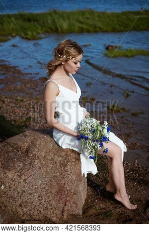 A Young Woman Alone, In A White Dress, Sits On A Stone On The Shore, Holding A Bouquet In Her Hand.