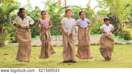 Group Of Childrens Playing Potato Sack Jumping Race At Park Outdoor During Summer Camp - Kids Having