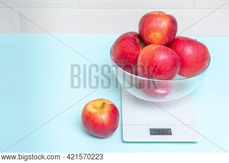 Red Apples In A Transparent Bowl On A Kitchen Scale, Copy Space, Close-up. The Concept Of Healthy Ea