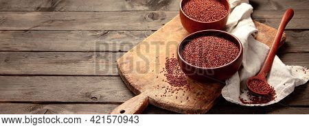 Red Quinoa Seeds On Wooden Background. Healthy Vegan Food Concept.