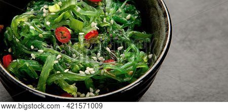 Wakame Seaweed With Sesame And Chilli On Gray Background. Asian Food Concept.