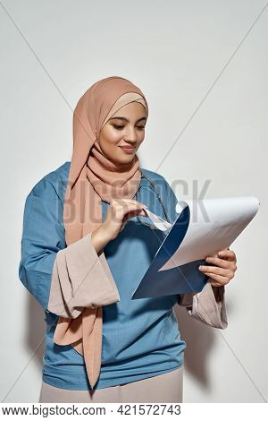 Cheerful Young Arabian Girl Doctor In Hijab Looking Into Notepad While Posing On Light Background, V