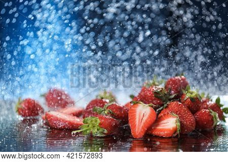 Big Red Strawberries Closeup Under The Water Drops In A Dark Blue Background. Healthy Lifestyle. Mul