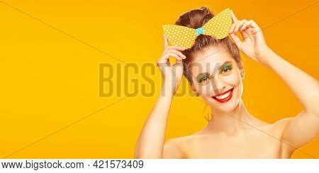 Portrait of an pretty young woman posing in paper bow in pin-up style on a yellow background. Beauty and pin-up style. Makeup and cosmetics. Studio shot. Copy space.
