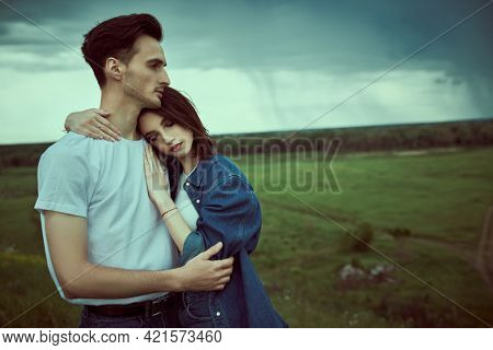 Beautiful couple of young people in jeans clothes standing in a valley hugging against a stormy sky. Beauty, fashion. Denim style. Relationships.