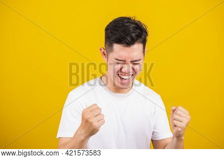 Asian Handsome Young Man Smile Positive Shaking Hands Enthusiastic Shouting Yes For Win Competition,
