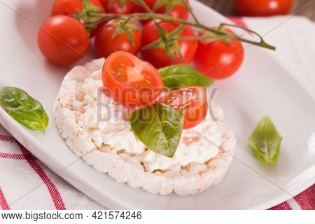 Rice Cakes With Milk Flakes And Tomato On White Dish.