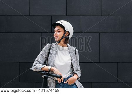 Young Woman Wearing A Scooter Helmet Standing At A Black Wall. Smiling Female In Casual Clothes Lean