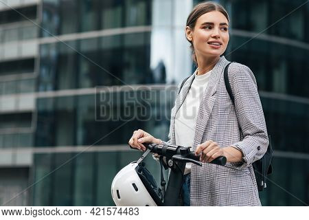 Portrait Of A Caucasian Businesswoman With An Electrical Scooter. Smilaing Female Holding A Scooter