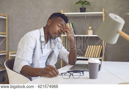 Tired Man Suffering From Computer Eye Strain Rubs Nose Bridge Sitting At Working Desk
