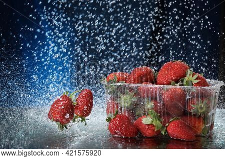 Strawberries In A Plastic Box Closeup Under The Water Drops In A Dark Blue Background. Healthy Lifes