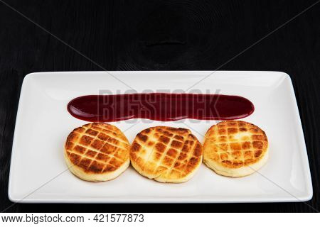 Cottage cheese pancakes on a dark background. Syrniki with berries jam on a white plate, food and drink concept