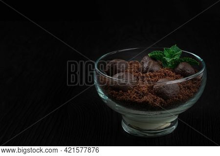 Chocolate dessert of cookies with pieces of chocolate and mint on a dark wooden background.