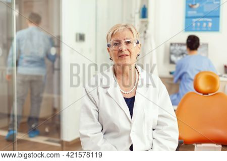 Portrait Of Specialist Senior Dentist Woman In Stomatological Office While Medical Assistant Discuss