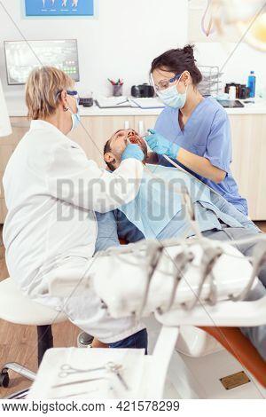 Stomatologist Senior Woman Performing Examination And Taking Care Of Teeth Using Dental Tools. Ortho